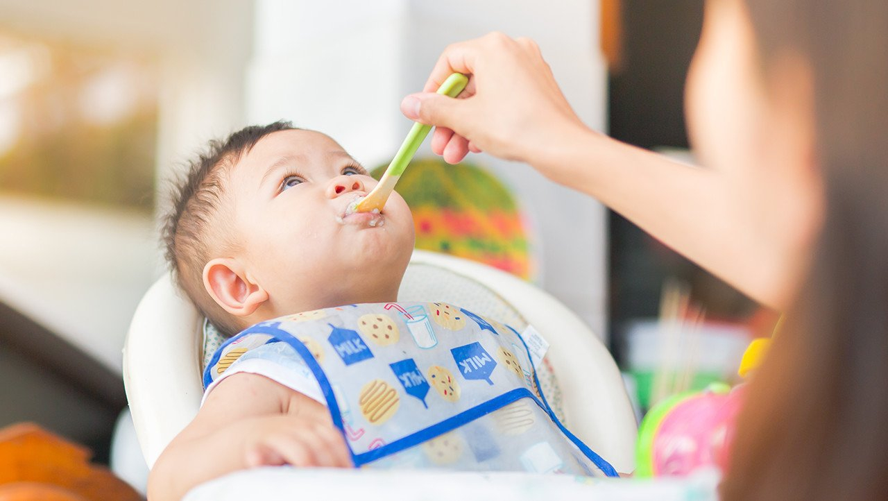 Bebé en una silla alta siendo alimentado con cuchara